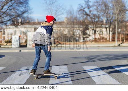 Teenager Skateboarder Boy With A Skateboard On Asphalt Playground Doing Tricks. Youth Generation Fre
