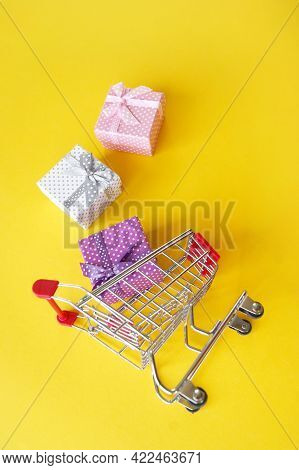 Mini Shopping Cart With Small Gifts On A Yellow Background. The Concept Of Shopping For Gifts For Th