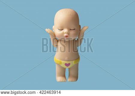 Little Doll Toy On Blue Background Is Isolate.