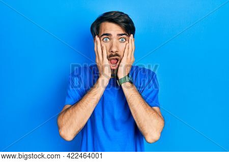 Young hispanic man wearing casual clothes afraid and shocked, surprise and amazed expression with hands on face