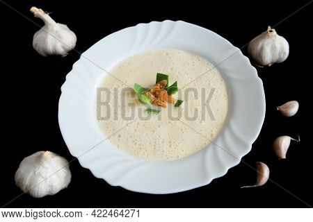 Garlic Cream Soup Decorated With Roasted Garlic And Leek In White Plate On Black Background. Culinar