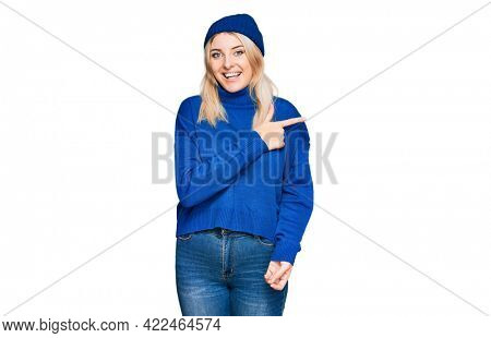 Young caucasian woman wearing wool winter sweater and cap cheerful with a smile of face pointing with hand and finger up to the side with happy and natural expression on face