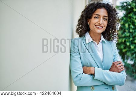 Young hispanic business woman wearing professional look smiling confident at the city leaning on the wall