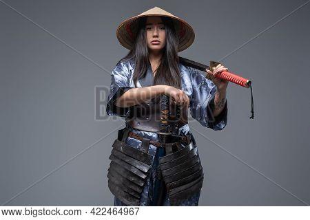 Japanese Female Killer With Katana Posing Against Gray Background