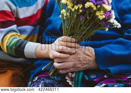 Close Up Female Senior Hand Holding Kid Hand And Flowers Bouquet. Preschooler Boy Supporting His Gre