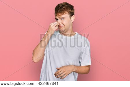Young caucasian man wearing casual white t shirt smelling something stinky and disgusting, intolerable smell, holding breath with fingers on nose. bad smell
