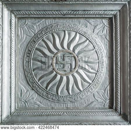 Swastika sign embossed on a silver metallic plaque. Decorative antique hindu religious motifs or symbols from temple.