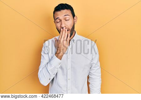 Hispanic man with beard wearing business shirt bored yawning tired covering mouth with hand. restless and sleepiness.