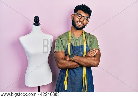 Arab man with beard dressmaker designer wearing atelier apron happy face smiling with crossed arms looking at the camera. positive person.
