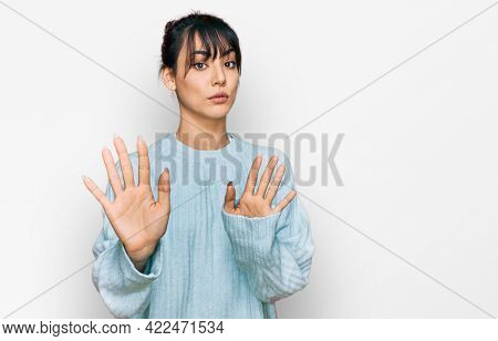 Young hispanic woman wearing casual clothes moving away hands palms showing refusal and denial with afraid and disgusting expression. stop and forbidden.