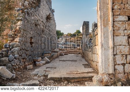 Urban Road In Ancient City Kanli Divane Or Canytelis, Ayaş, Turkey. Remains Of Buildings On Both Sid