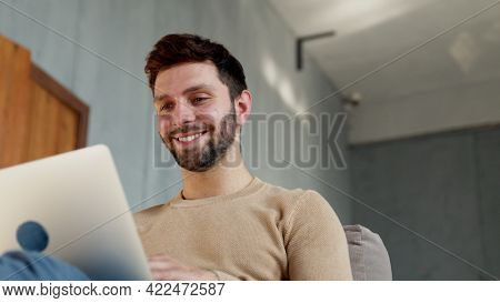Happy man with laptop in apartment