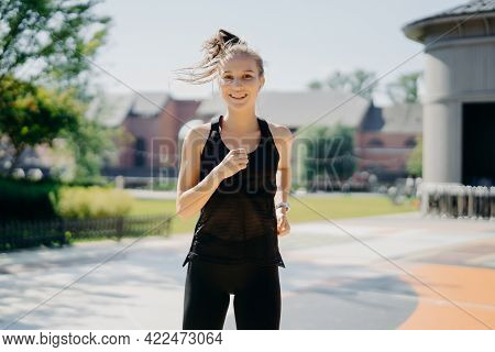 Happy Energetic Sportswoman Runs On Stadium Has Pony Tail Floating On Wind Dressed In Activewear Bei