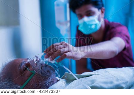 Son With Medical Face Mask Taking Care Of Sick Old Father At Hospital By Checking Ventilator Oxygen