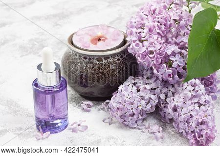 Essential Aroma Oil, Aromatic Candle, Lilac Flower For Aromatherapy, Spa, Massage On Gray Concrete B