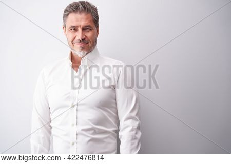 Business portrait - businessman smiling. Mature age, middle age, mid adult man in 50s with happy confident smile. Copy space.