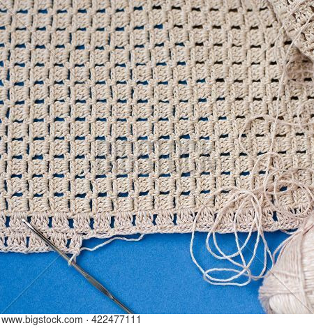 Crochet With Beige Cotton Threads On A Blue Background.