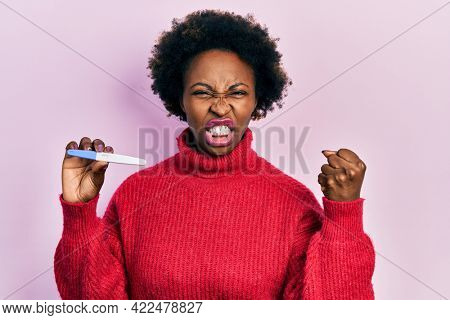 Young african american woman holding thermometer annoyed and frustrated shouting with anger, yelling crazy with anger and hand raised