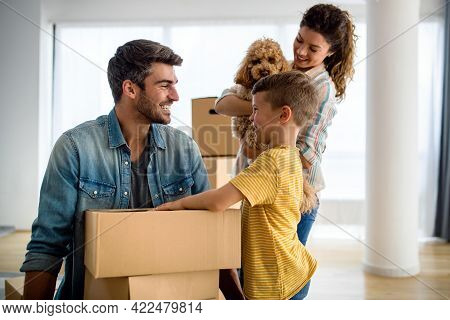 Happy Family With Cardboard Boxes In New House At Moving Day.