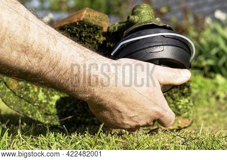 A Man Winds A New Bobbin On A Mowing Trimmer