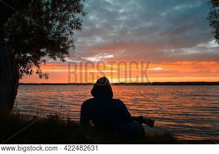 Man Relaxing By The Lake At Sunset. Silhouette Of Person Lying And Looking At The Setting Sun. Enjoy