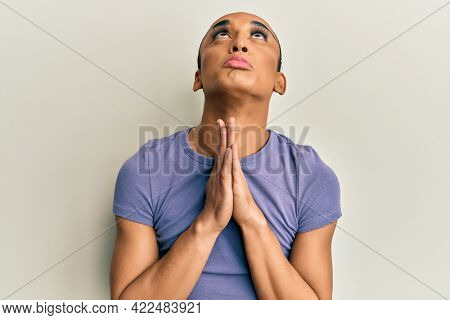 Hispanic man wearing make up and long hair wearing casual t shirt begging and praying with hands together with hope expression on face very emotional and worried. begging.