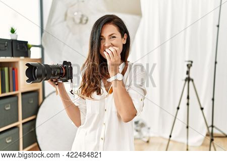 Beautiful caucasian woman working as photographer at photography studio laughing and embarrassed giggle covering mouth with hands, gossip and scandal concept
