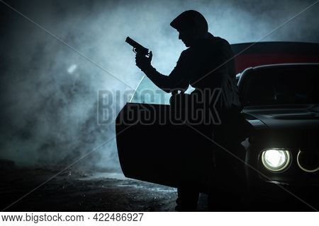 Caucasian Pensive Gangster In His 40s Playing With His Handgun During Late Night. Seating On His Car
