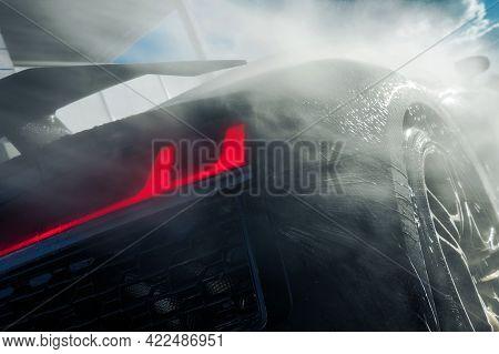 Powerful Pressure Washing Of Rear Of Performance Car. Car Wash Theme.