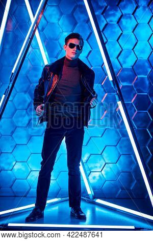 Men's style and fashion. Full length portrait of a courageous handsome man in black sunglasses and black leather jacket posing among the neon lamps. Futurism, techno style.