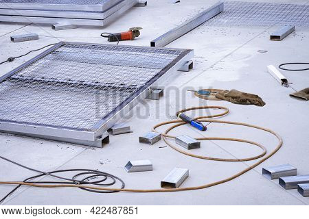 Steel Mesh Fence Panels, Electrode Holder, Red Angle Grinder With Various Hand Tools On Concrete Flo