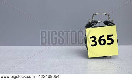 An Alarm Clock With A Sticky Note Written With 365 Represent Days In A Year On Grey Background With