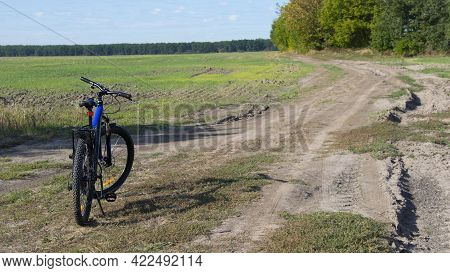 Bike Stands On The Road In The Field. A Mountain Bike Stands On A Field Path With Green Grass. Cycli