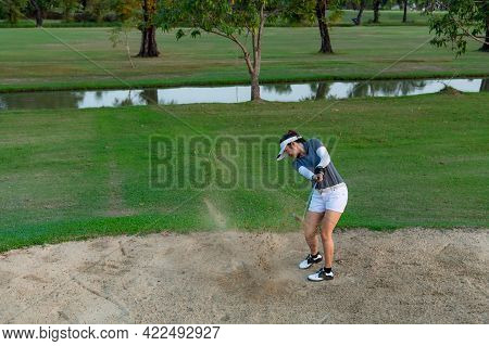 Golfer Woman Chip Golf Ball Out Of A Sand Trap. People Swing And Hitting Golf Course Is On The Fairw