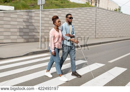 Young Black Woman Assisting Visually Impaired Millennial Guy With Cane Crossing City Street. Vision