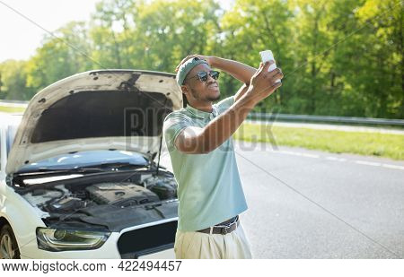 Upset Black Guy Standing Near Broken Car With Open Hood, Having Problem, Trying To Find Mobile Netwo