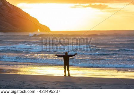 man arms outstretched by the ocean at sunset