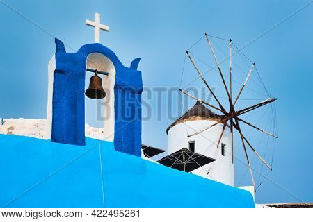 Old traditional whitewashed greek windmill and orthodox christian church bell on Santorini island in Oia town. Oia village, Santorini, Greece