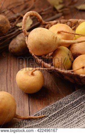 Basket with fresh organic yellow turnips on wooden background