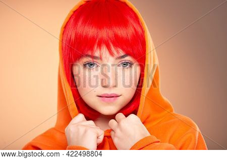 Closeup portrait of an young  girl with a red hair over colored background. Pretty teen girl with  freckles on face. Beauty portrait.  Photo of a young fashion model in orange clothes.