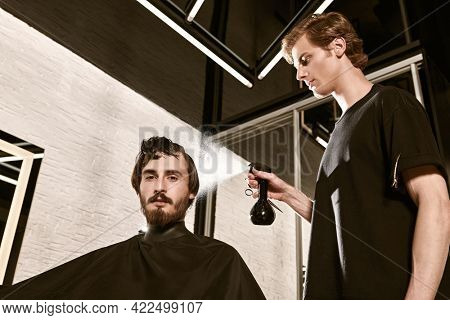 Good looking young man visiting hairstylist in barbershop. The hairdresser moisturizes the hair of the male client while cutting.