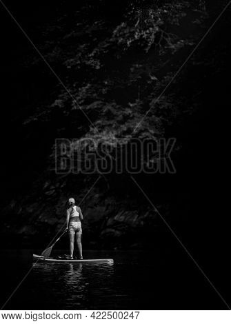 Unidentifiable woman on a paddle board exploring the shoreline black and white