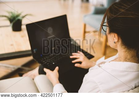 Over the shoulder view of middle-aged business woman working at home using laptop