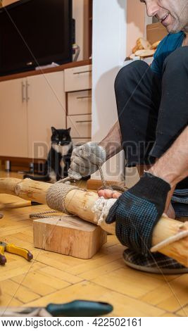Middle-aged Man Making Homemade Cat Tree For Lovely Pet. Vertical Photo.