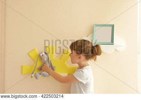 Girl Happy Lifestyle Puts A Gray Hare On A Shelf In The Form Of A Yellow Sun. Children's Shelves In