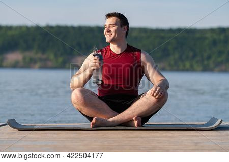 Young Man Drinks Water From A Reusable Bottle After Yoga Class On The River Bank. The Concept Of Los