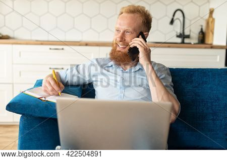 Cheerful Redhead Bearded Male Entrepreneur Sitting On The Sofa With A Laptop On His Laps, Man Talkin