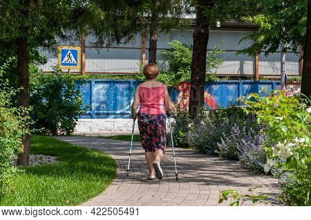 Krasnodar, Russia - June 1 2021: Active Senior Woman Practicing Nordic Walking With Poles Outdoors I