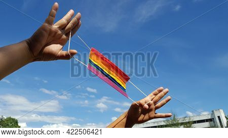 Hands Hold A Colorful Mask With Blue Background. A Concept Is For Pride Month And Encourage Lgbtqia