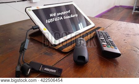 Teaching Tools Including A Tablet, A Slide Controller And A Tv Remote Are On An Aged Wooden Table, A